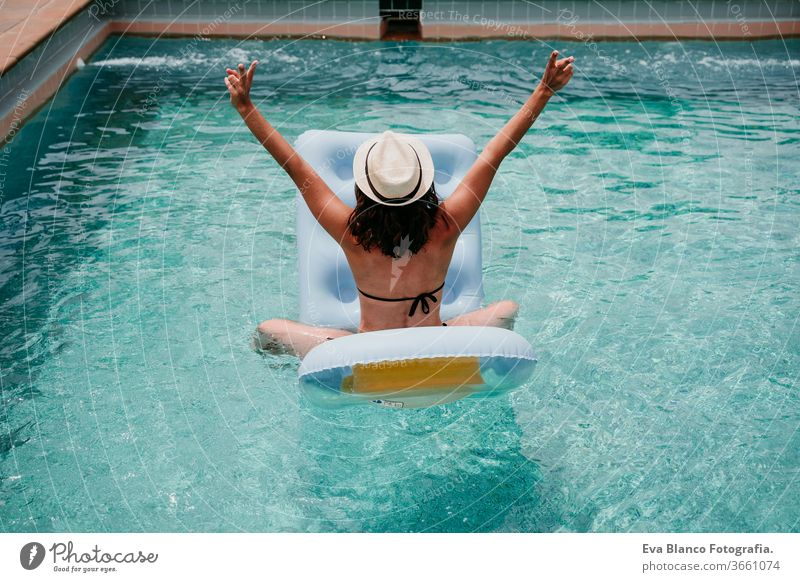 happy woman on inflatable having fun. Summer time. back view swimming pool summer blue water relax hat sexy lifestyle sunglasses swimwear hot body tanning spa
