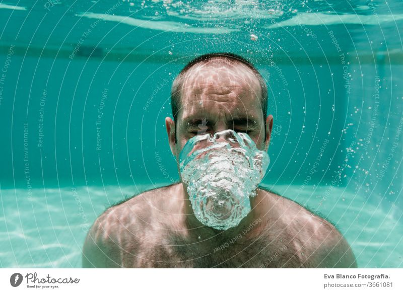 young man diving underwater in a pool making bubbles, summer and fun lifestyle swimming caucasian dive clear health light action wet swimmer blue active float