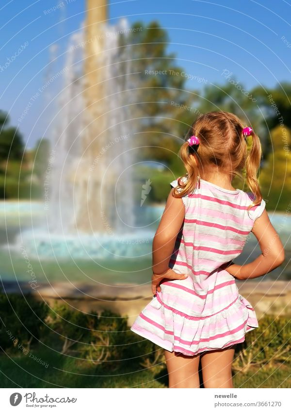 Preschooler little girl watching fountain rear view. Young female child enjoy being outside in summertime. Curiosity blonde looking at splashing droplets. enjoyment of holidays. Pretty kid photography