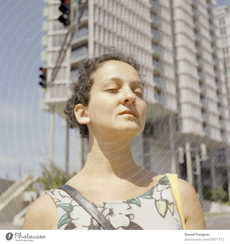 Young woman enjoys sun rays during a break. Contemplation and serenity concept. Shot on analog medium format film portrait young beauty beautiful face fashion