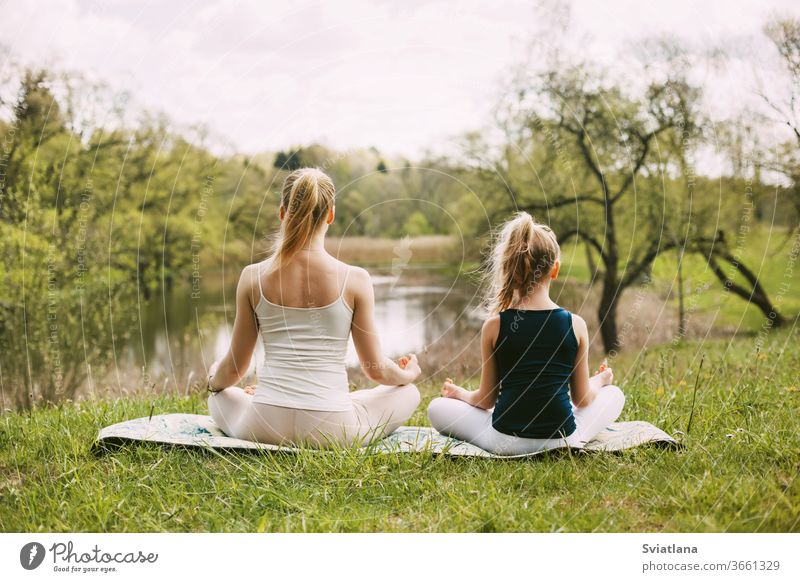 Mother and daughter sit in the Lotus position in the garden. The family practices yoga outdoors. Back view, space for text meditation lotus together mum