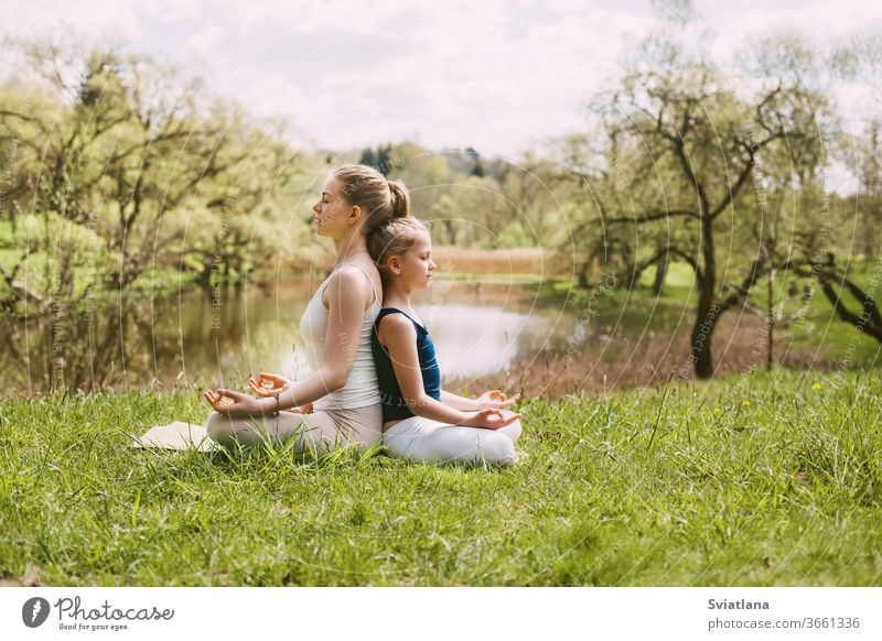 A beautiful young woman and a fair-haired girl are meditating in the Lotus position. Family vacation, meditation. Side view, space for text yoga outdoor lotus