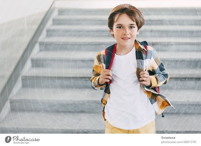 A happy boy with a backpack stands on the steps in front of the entrance to the school and smiles beautifully. Beginning of the new school year after the summer holidays. Back to school