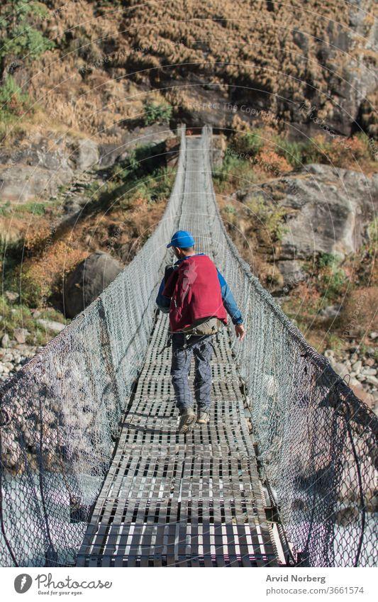 Adventurer trekking across a suspension bridge, Annapurna circuit, Nepal activity adventure along annapurna circuit backpack backpacker buddhism challenge