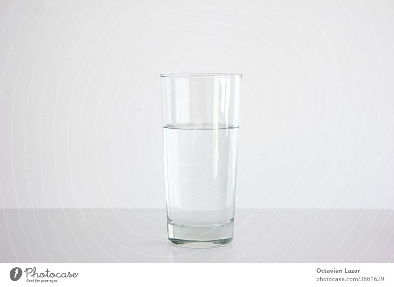 Clear glass three quarters full of water set on white table isolated close up frontal shot element view drinkable clean drought ecology waste liquid beverage