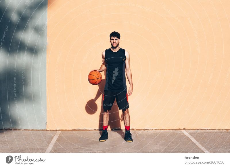 basketball player with the ball in front of a wall sport competition game athletic competitive playing exercise male exercising effort hobby match practicing