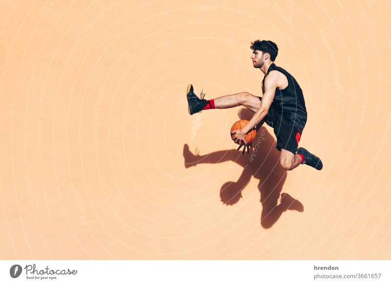 basketball player jumping with the ball in his hands in front of a wall sport competition motion game athletic competitive playing exercise male exercising