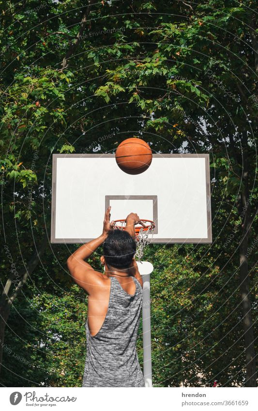 young man in front of the basket throwing the ball sport basketball competition game athletic competitive play playing exercise male exercising effort hobby