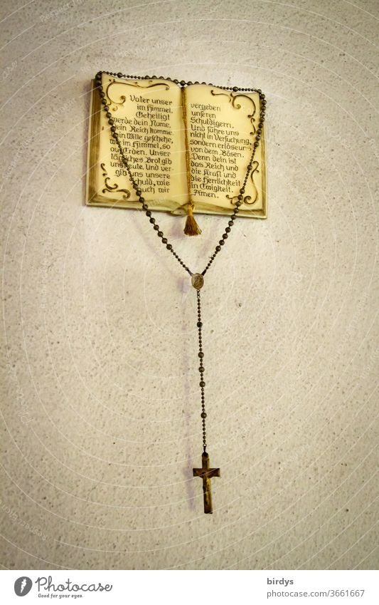 A rosary hangs from an open Christian prayer book with the Our Father - prayer Rosary Lord's Prayer Bible Christianity Religion and Faith Catholicism