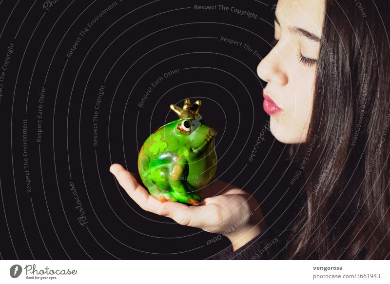 Close-Up of young girl kissing a frog sculpture against black background Kissing teen teen girl teenage girl teenager one girl only brunette hair long hair