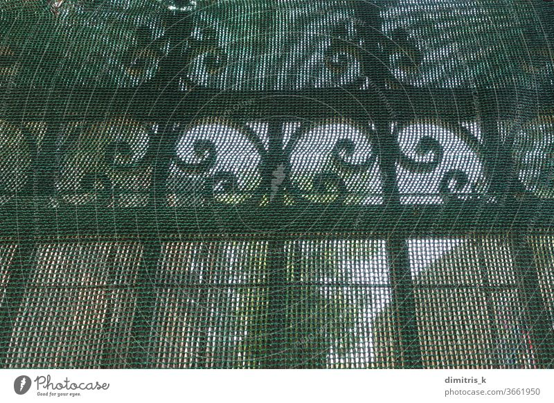antique metal fence railings under transparent debris netting wrought iron behind pattern decorative ornamental motif rusty old vintage dust abandoned the past
