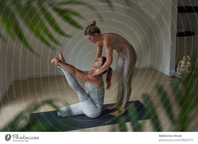 Focused women performing Krauncasana stretching yoga pose practice studio flexible calm heron well being balance wellness female instructor fit sportswear