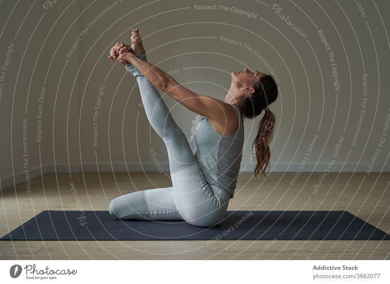 Focused woman performing Krauncasana stretching yoga pose practice studio heron flexible calm well being balance harmony wellness female fit sportswear healthy