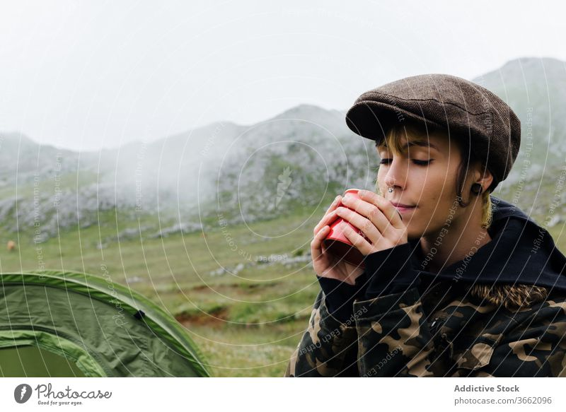 Woman in outerwear near camping tent in nature woman highland content relax traveler morning wanderlust freedom landscape harmony joy casual countryside cold