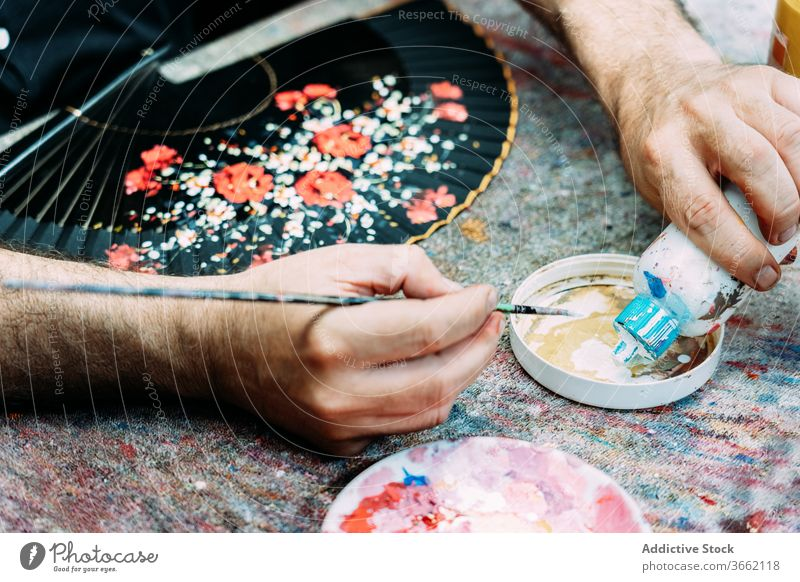 Crop artist pouring white gouache into palette while painting waver draw paintbrush artwork hand fan process floral pattern skill designer decor occupation