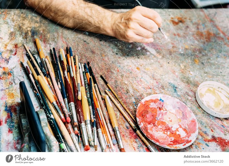 Crop artist hand with paintbrush above worktop multicolored palette draw creative artwork occupation profession pigment watercolor painter professional