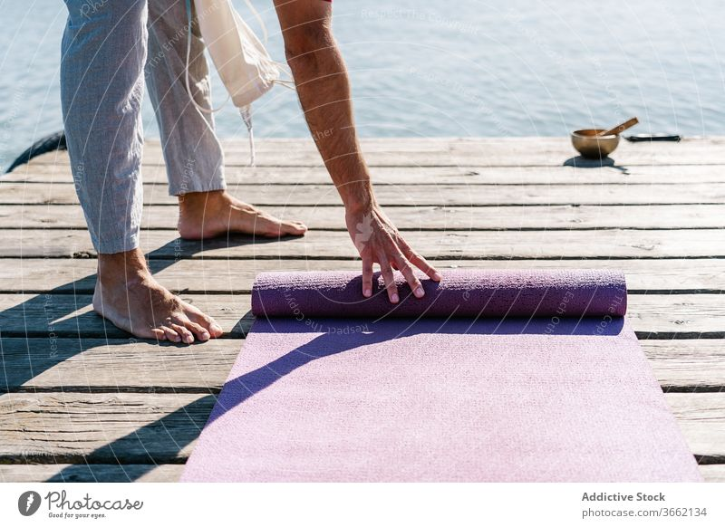 Man with yoga mat on pier on sunny day man singing bowl meditate wooden embankment sea healthy practice harmony relax male casual barefoot balance wellness