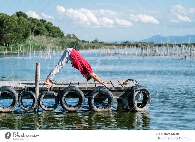 Fit man improving balance while doing Natarajasana yoga pose on sea embankment natarajasana lord of the dance gyan mudra stretch pier peaceful practice harmony