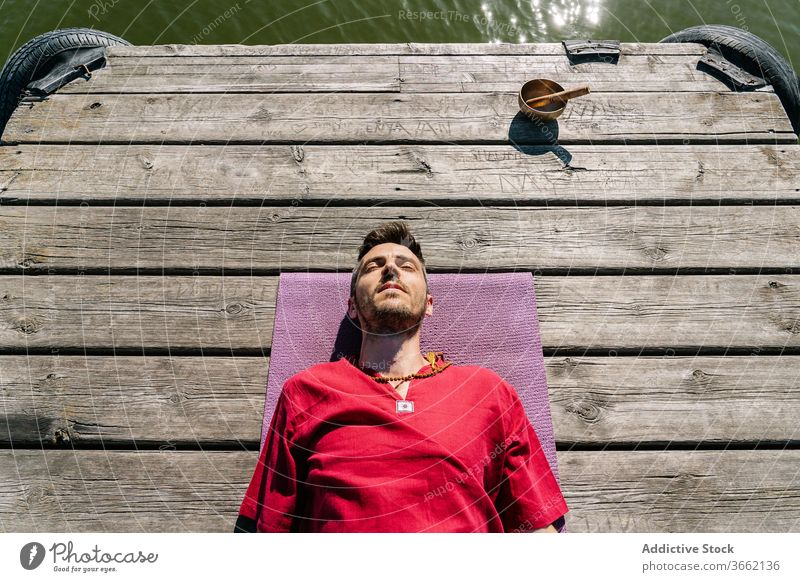 Relaxed man meditating on wooden pier near singing bowl after yoga training lying mat meditate relax embankment recreation eyes closed seaside session male