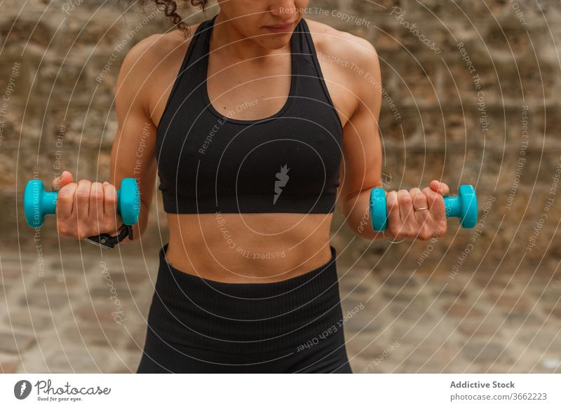 Fit ethnic sportswoman training with dumbbells on embankment during workout squat balance reached arm pavement stretch practice flexible activewear strong