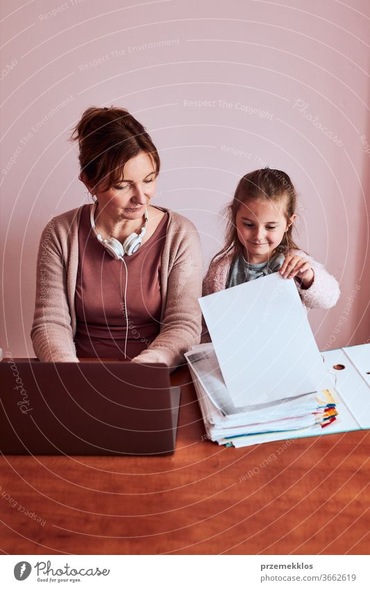 Woman working talking doing her job remotely during video chat phone call on laptop from home. Woman sitting at desk in front of computer looking at screen using headphones and smartphone while her daughter playing around. Concept of remote working