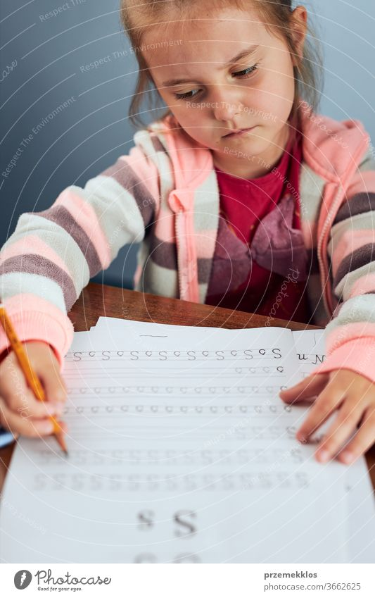 Little girl preschooler learning to write letters reluctantly. Kid writing letters, doing a school work unwillingly. Concept of early education attention
