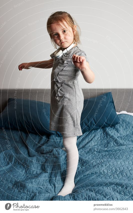 Little girl singing holding headphones cord imitating herself a real singer. Child having fun jumping dancing listening to music on bed in bedroom at home child