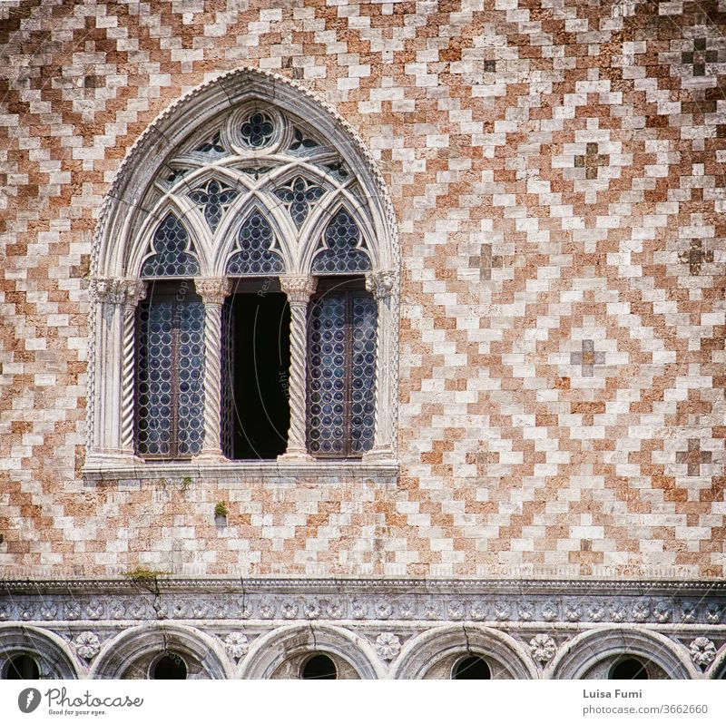 Venice, palazzo Ducale: detail of tripled arcade window and facade decoration with alternate red marble and white stone brick paving, soft focus Doge's Palace