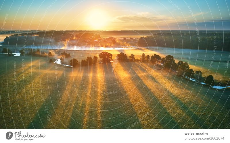 First sunrays over green meadow and field. Sunny summer calm morning panorama. fog river nature landscape sunrise cloud tree background environment mist aerial