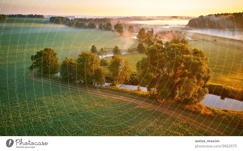 Sunny summer mist morning. First sunrays over green meadow and field fog river nature landscape sunrise cloud tree background environment panorama aerial creek