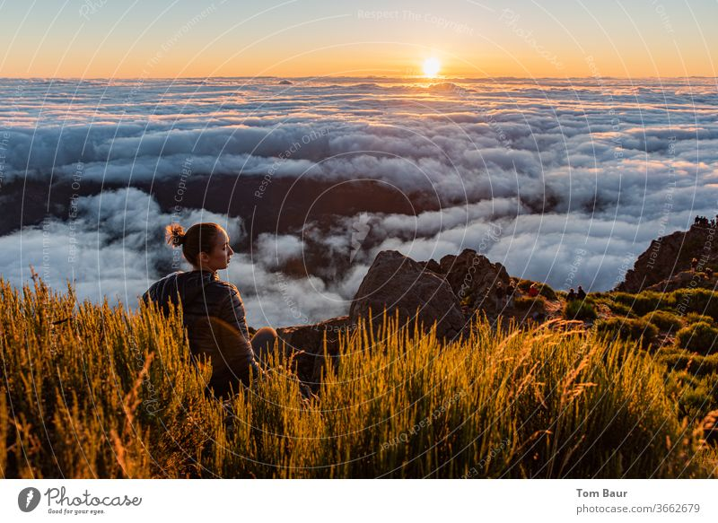 young woman at the edge of a mountain peak sits above the clouds and watches the sunrise. The rising sun on the horizon close above a dense carpet of clouds