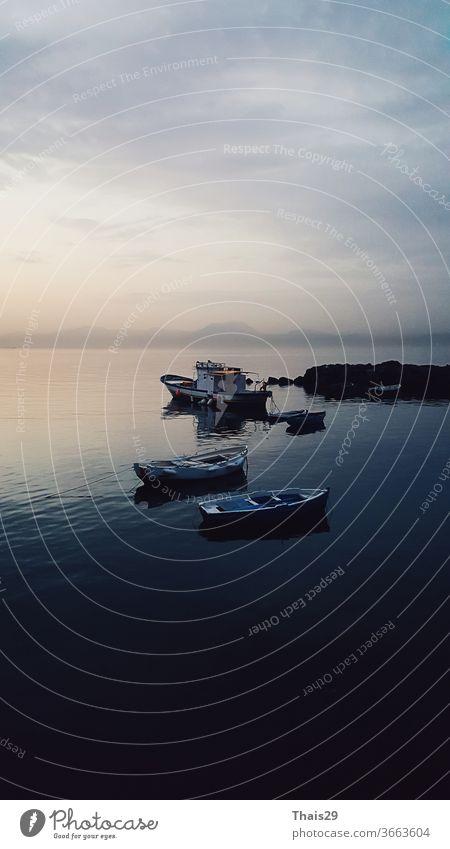 early sunrise quiet sea, no waves, sun light reflecting on water, small fisherman boats resting, beatiful horizon marine sea landscape view, Italy, Napoli, Naples