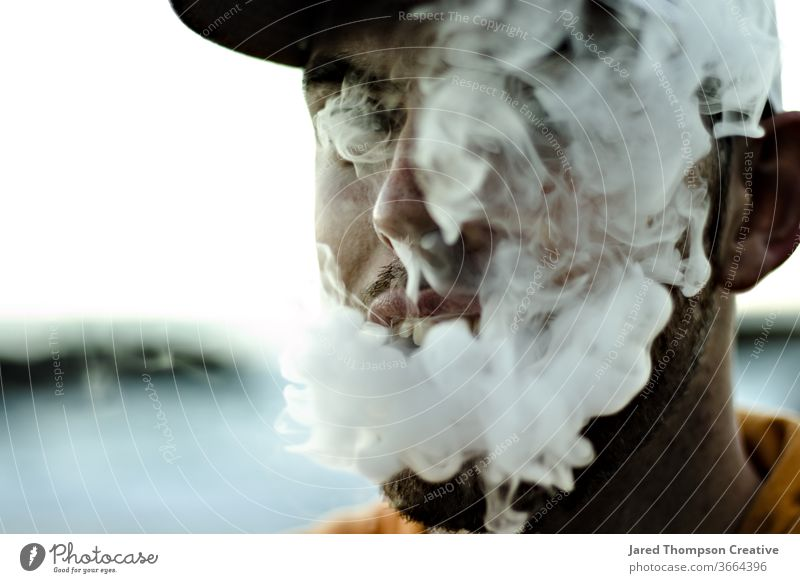 A young, bearded man blowing thick smoke out of his mouth from a vape. smoking cloud youth adult teenager Smoke Cigarette Smoke cloud Smoky Addiction