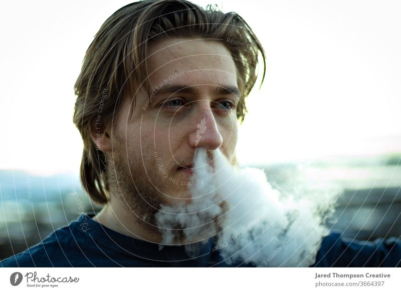 A young man blowing smoke out of his nose. vape youth culture Cigarette Smoking Adults Youth (Young adults) Cigarette smoke smoke trick