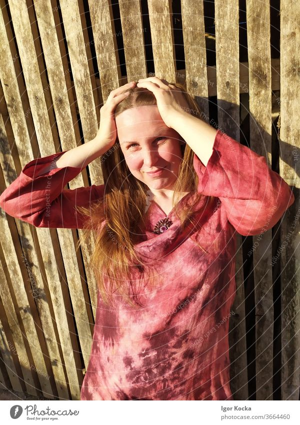 Portrait Of Smiling Woman Standing Against Wooden Wall Portrait photograph Beautiful Pink Color Wooden wall Looking into the camera Front view waist up