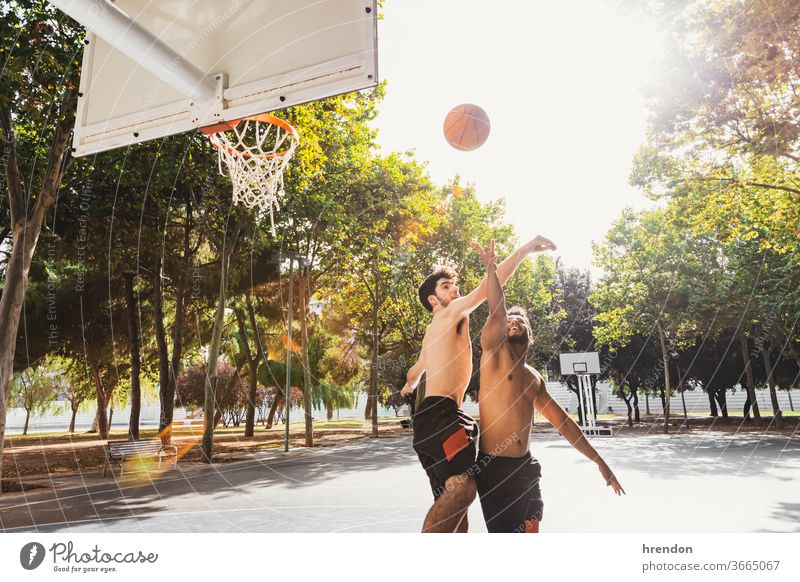 two young men play basketball outdoors sport competition game athletic competitive playing exercise male exercising effort hobby match practicing sporting