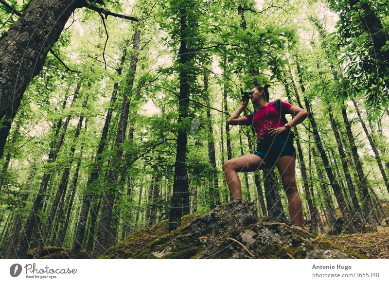 Girl Scout with a backpack looking at the forest with goggles girl scout exploring person explorer survival discovery extreme model expression freedom