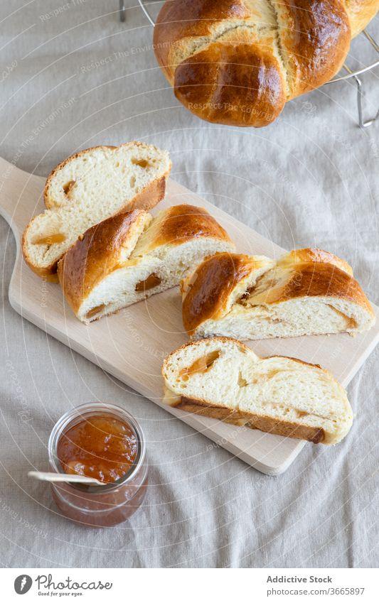 Brioche on wooden board near jam in jar brioche bun delicious homemade gastronomy slice pastry sweet glass jar baked goods cutting board cuisine yummy bakery