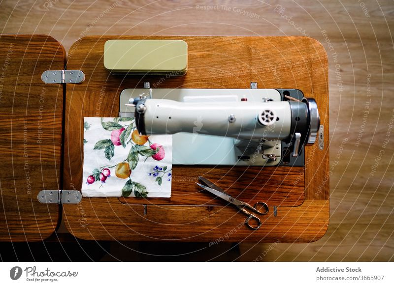 Sewing machine and fabric sample with fruit pattern in workshop sewing machine scissors craft equipment small business studio sharp instrument professional