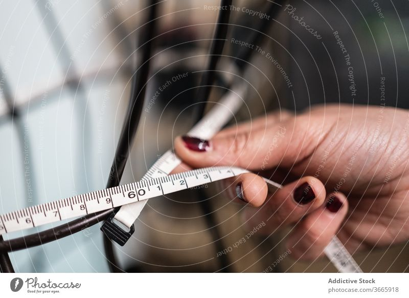 Anonymous woman taking measurements in a wired dummy fashion clothing meter metal figure sewing mannequin measuring form designer boutique shape scissors
