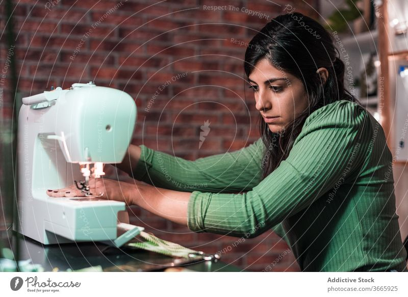 tailor sewing on machine near brick wall in atelier sewing machine handicraft sample pattern lamp small business workshop fabric artisan using equipment process