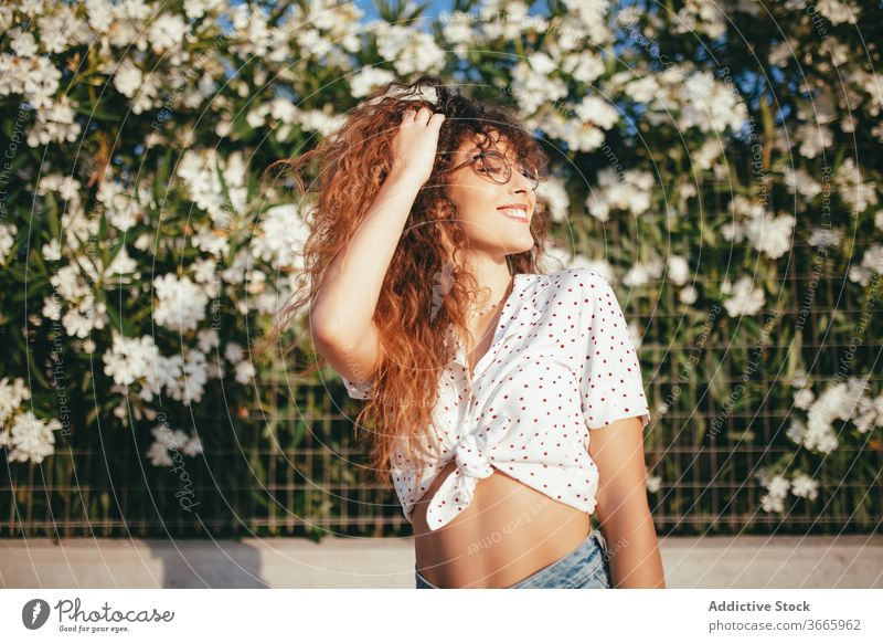 Positive female with wavy hair standing near blooming flowers woman touch hair fence happy beauty lifestyle belly idyllic feminine summertime toothy smile
