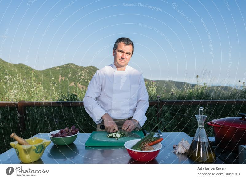 Male cook cutting vegetables for dinner preparation in outdoor kitchen man cucumber chef prepare dish fresh healthy food work cuisine male middle age pensive