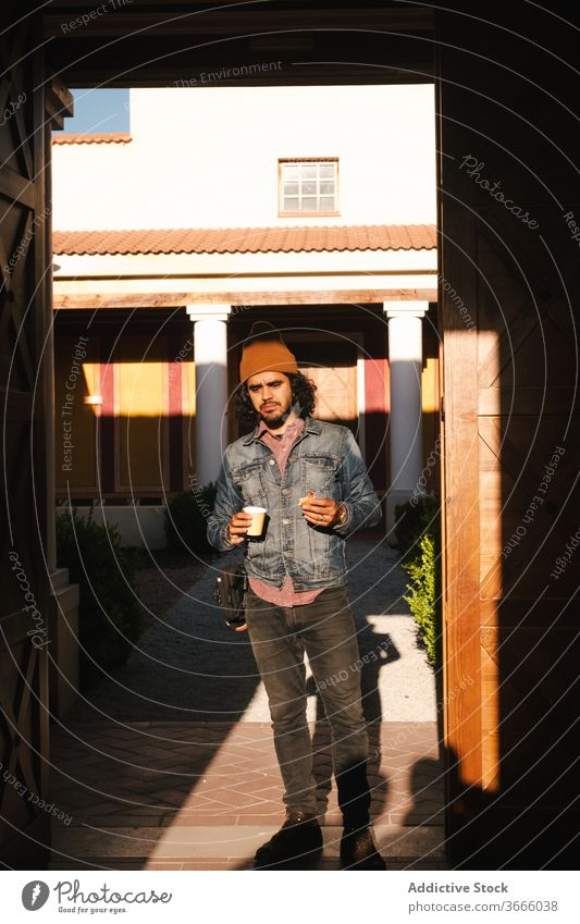 Man with paper cup against building with pillars man refreshment drink positive street exterior hipster coffee break content outfit colorful evening sunlight