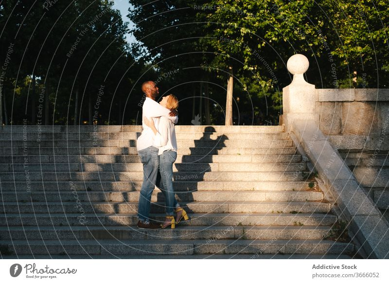 Cheerful loving multiethnic couple on street stairs walk urban hugging love cheerful relationship gentle carefree staircase evening madrid spain content