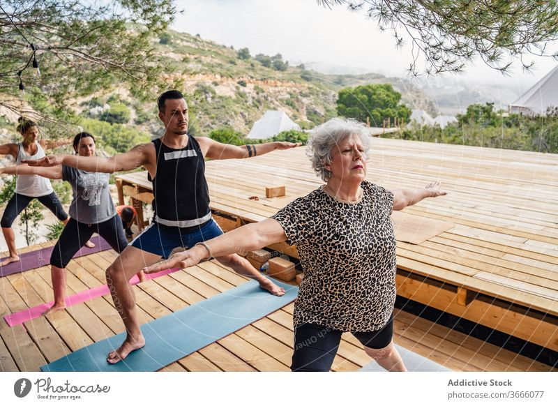Team of active people doing Warrior II yoga asana in camp warrior ii virabhadrasana b stretch wellness healthy balance class practice wellbeing vitality zen