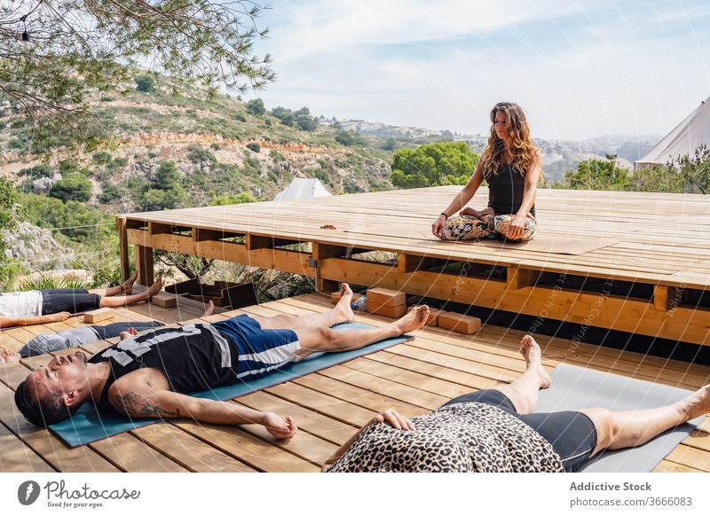 Group of yoga trainers meditating in Savasana position during class with instructor people corpse savasana lotus pose camp meditate recreation relax healthy