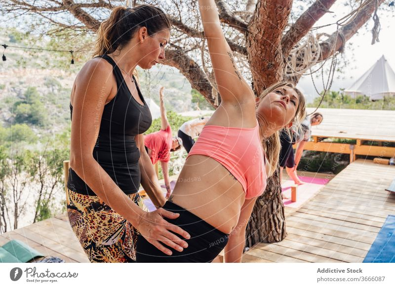 Concentrated woman doing yoga with trainer in park women side angle parsvakonasana support instructor class wellness healthy help wellbeing balance exercise