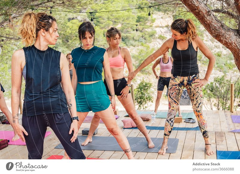 Group of young women warming up before yoga class in park warm up instructor wellness practice stretch nature group together teacher concentrate flexible