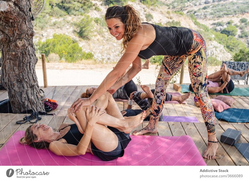 Happy woman stretching legs during yoga class with trainer women supine pigeon supta kapotasana wellness healthy positive together help exercise vitality